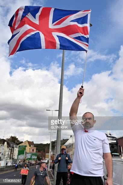 An anti-immigration protester waves a Union flag at a gathering in Dover on the south-east coast of England, on September 5 as pro-and anti-migrant...