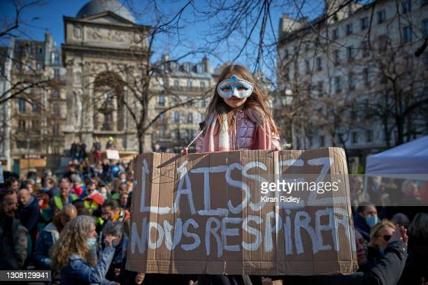 An Anti-Lockdown and Anti-Vaccination protestor holds a sign reading 'Let us breathe' during an Anti-Lockdown demonstration in Paris on the first day...