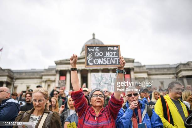 An anti-mask protester holds a sign reading 'We Do Not Consent' while a woman next to her coughs at the Unite for Freedom protest in Trafalgar Sq on...
