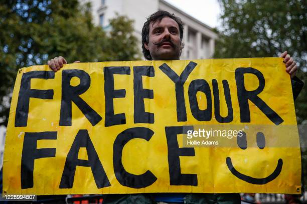 An anti-mask protestor holds a sign during a rally outside Downing Street on October 10, 2020 in London, England. Demonstrators rallied against the...
