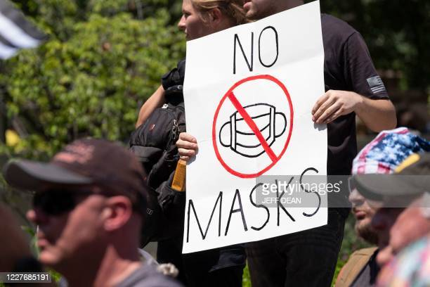 "An anti-mask protestor holds up a sign in front of the Ohio Statehouse during a right-wing protest ""Stand For America Against Terrorists and Tyrants""..."