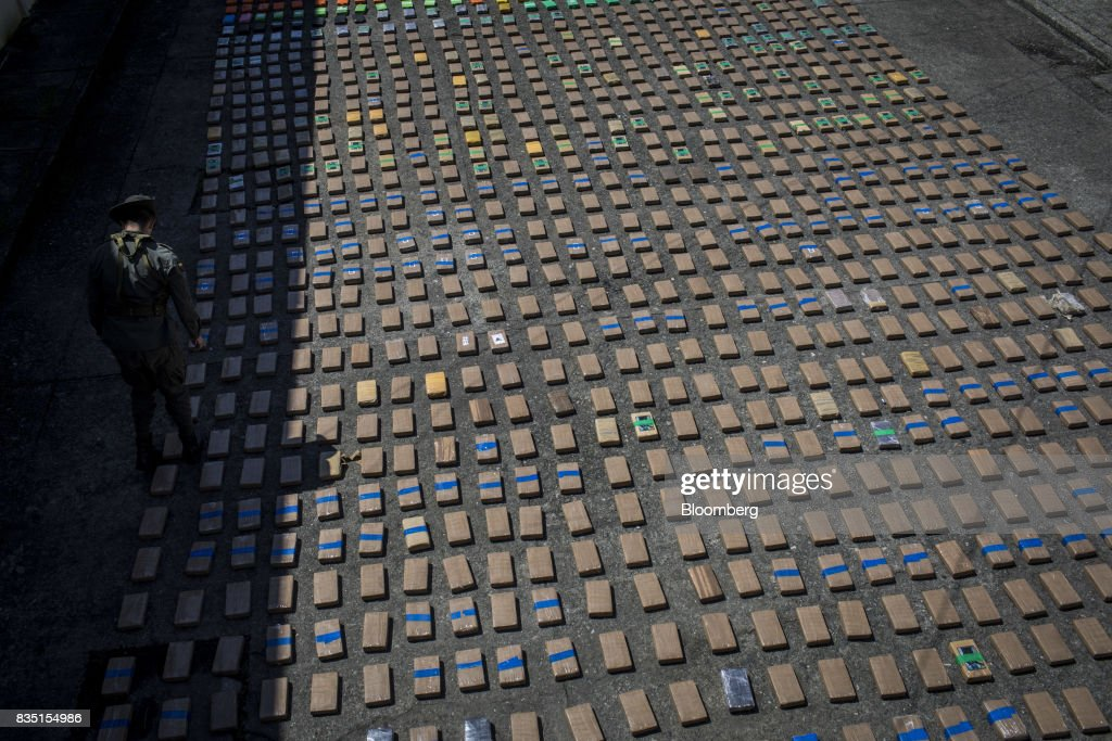 An anti-narcotics police officer stands guard over packages of cocaine, seized from inside a shipping container at the Buenaventura port, in Buenaventura, Colombia, on Thursday, Aug. 10, 2017. The United Nations Office of Drugs and Crime (UNODC) released a report stating that coca crops in Colombia has increased over fifty percent in one year. The Trump administration has been putting pressure on Colombia to curb the flow of drugs into the U.S. Photographer: Nicolo Filippo Rosso/Bloomberg via Getty Images