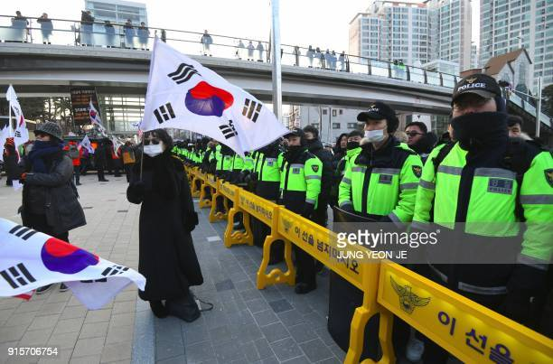 An antiNorth Korea protester waves a South Korean flag in front of a police line during a rally against planned North Korea's musical concert near...