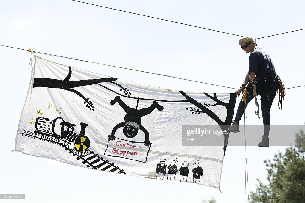 An anti-nuclear activist fixes a banner reading 'Stop the Castor' as he protests against an ultimate storage facility for nuclear waste in a salt deposit in Gorleben, western Germany, on June 5, 2010. Since more than 30 years, environmentalists protest against the storage which is already used as interim storage facility.