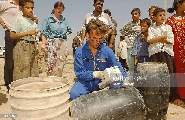 An Antinuclear activist from Greenpeace checks a barrel during a campaign to replace barrels contaminated with radioactive yellowcake that were...