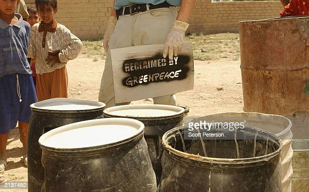 An antinuclear activist from Greenpeace prepares to mark some reclaimed barrels during a campaign to replace barrels contaminated with radioactive...