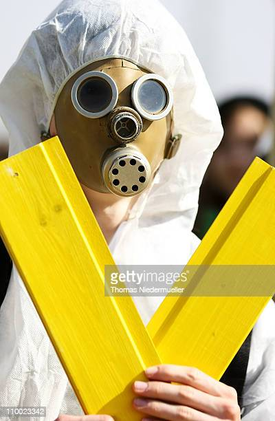 An antinuclear activists wearing a gas mask holds a yellow Xsign as a symbol of the antinuclear movement in front of the Neckarwestheim nuclear power...
