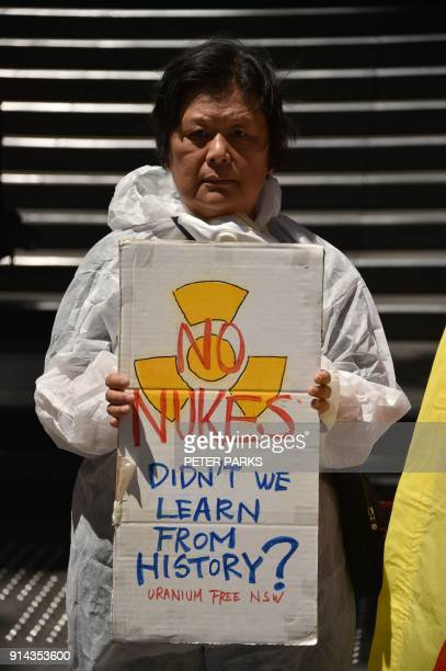 An anti-nuclear protester holds up a placard outside the Australian government offices in Sydney on February 5, 2018. Members of the group...