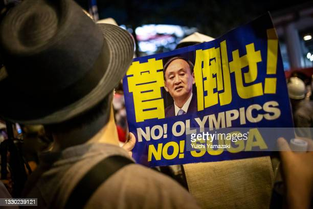 An anti-Olympics protester holds a placard with a picture of Japanese Prime Minister Yoshihide Suga during the opening ceremony of Tokyo Olympics on...