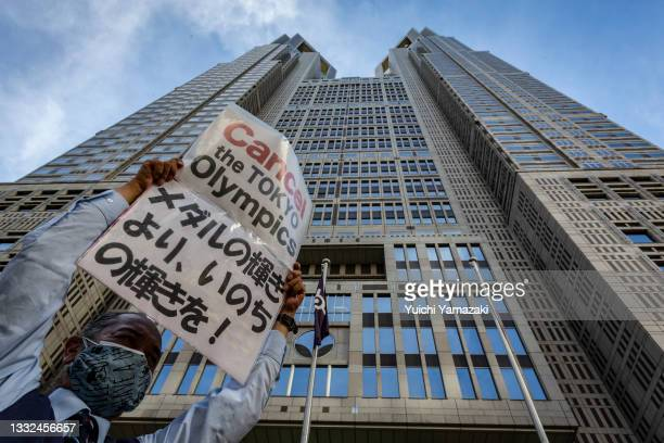 An anti-Olympics protester holds up a placard saying 'Cancel the Tokyo Olympics' in front of the Tokyo Metropolitan government building on August 05,...