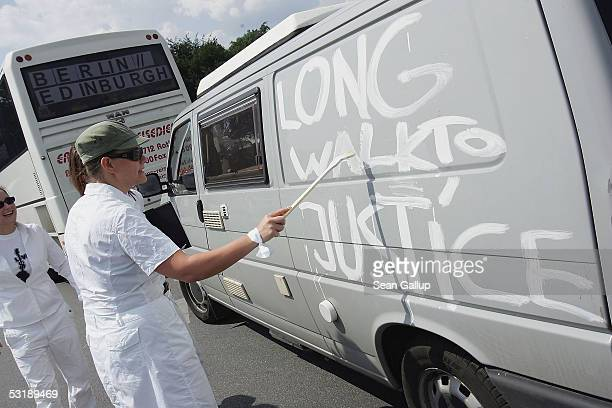 An antipoverty activist paints the slogan Long Walk to Justice on a van before it joined busses and cars embarking to Edinburgh July 3 2005 in...