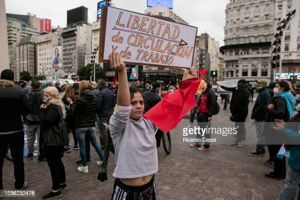 An antiquarantine protester holds a sign with a message that reads in Spanish 'Freedom to move and work' demanding the end of government's lockout...