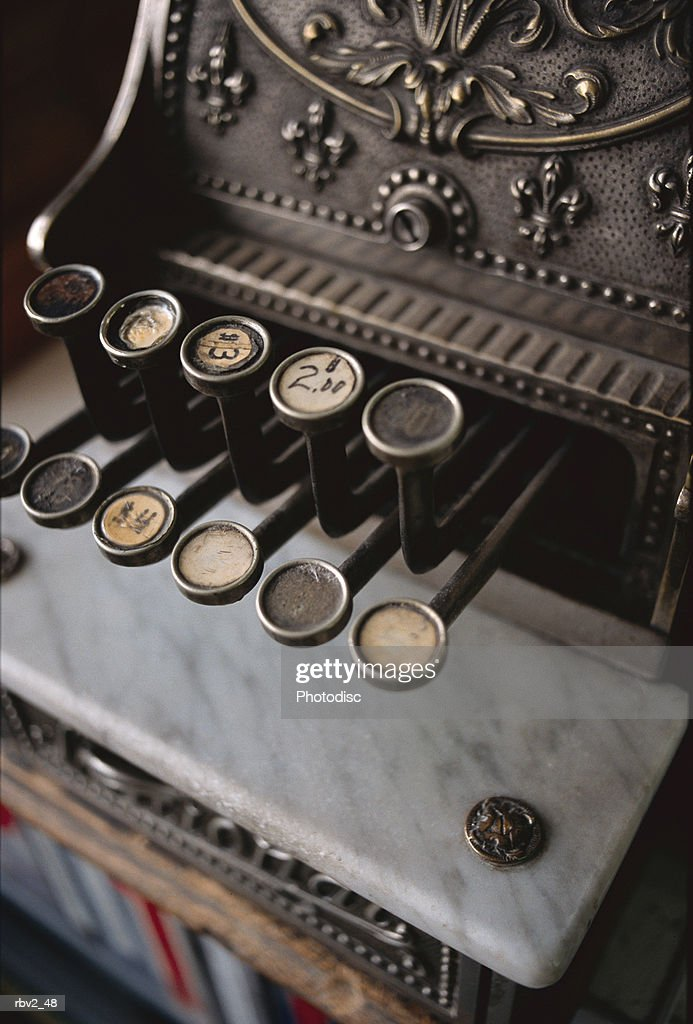 an antique cash register and its buttons sits on a black background : Foto de stock
