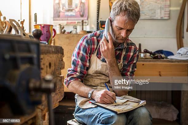 An antique furniture restorer in his workshop, using a smart phone.