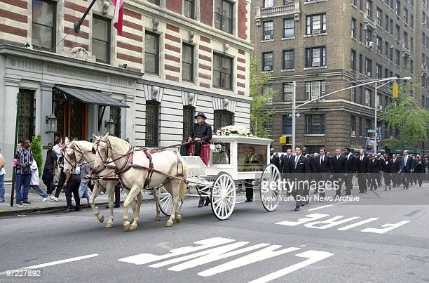 An antique glasspaneled carriage pulled by a pair of creamcolored horses bears the casket of RB star Aaliyah along Madison Ave from the Frank E...