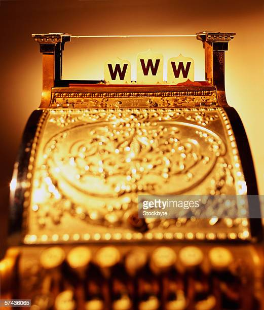 an antique golden cash register displaying the letters www