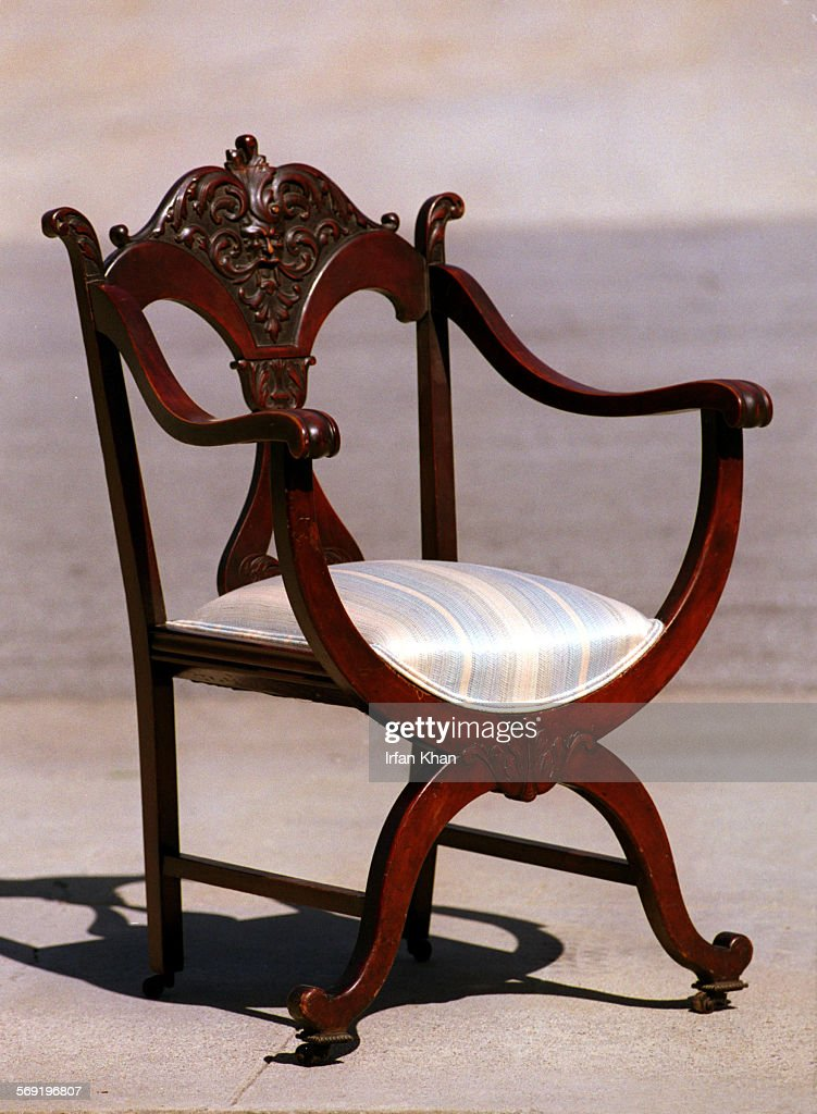 An antique hand carved wooden chair given to Dede Ginter(cq) by her grand - An Antique Hand Carved Wooden Chair Given To Dede Ginter By Her