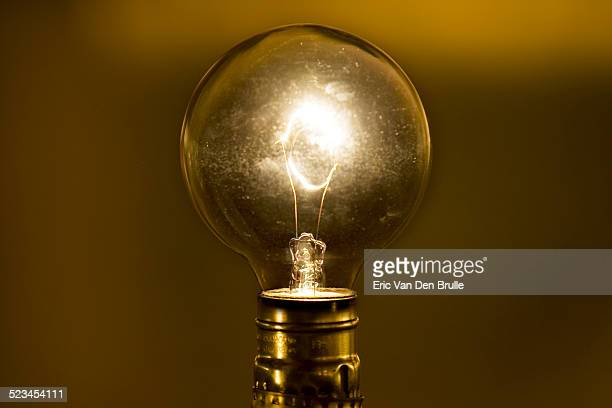 an antique lightbulb shining bright - eric van den brulle stock pictures, royalty-free photos & images