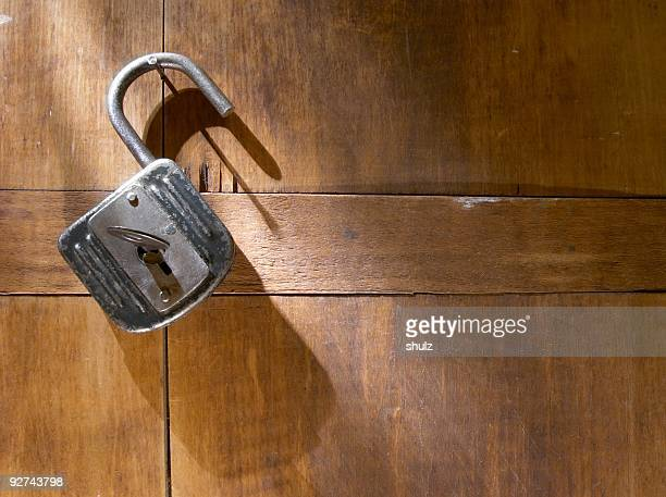 An antique padlock against a wood background