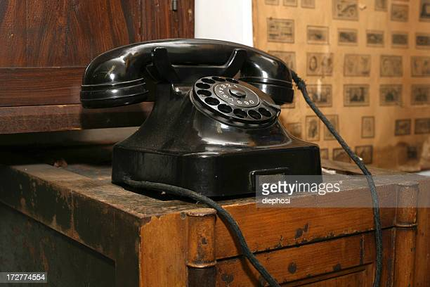 An antique telephone on a wooden table