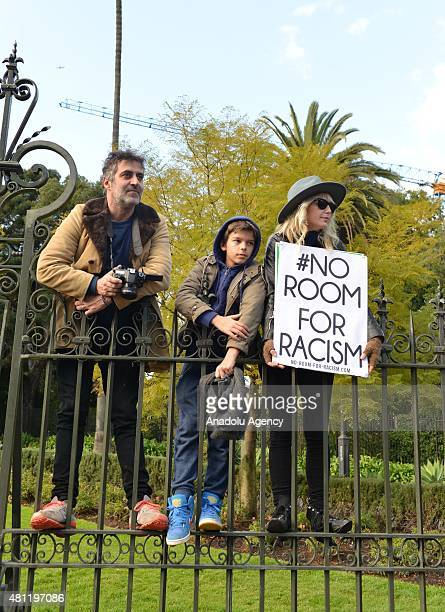 An antiracism activist holds a placard as antiIslam protesters stage rally in Melbourne Australia on July 18 2015 Hundreds of police were deployed in...