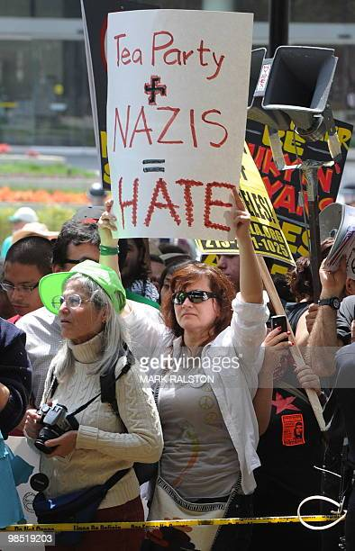 An antiracism protester holds up an antiTea Party placard behind a LAPD police line as members of the neonazi group The American National Socialist...