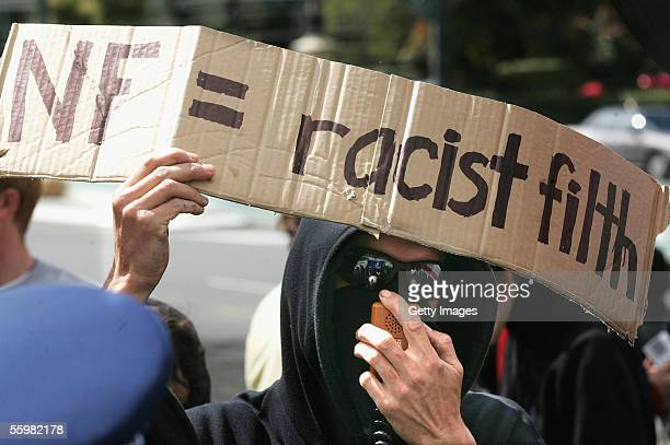 An antiracism supporter in the crowd shows his opposition to the National Front during a New Zealand National Front party rally at the Wellington war...