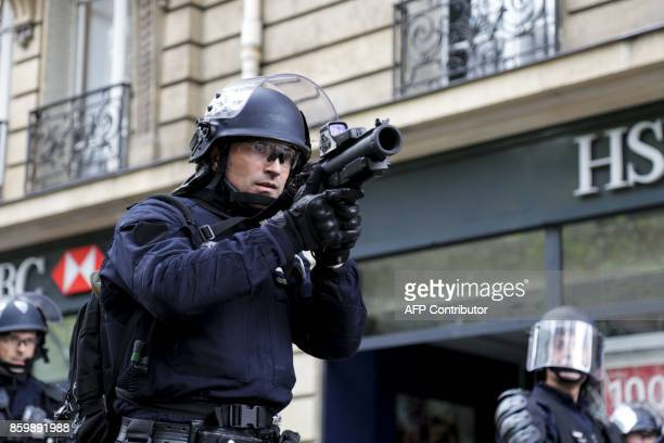 An antiriot police eye the situation on the sidelines of a demonstration on October 10 2017 in Paris part of a nationwide strikes and demonstrations...