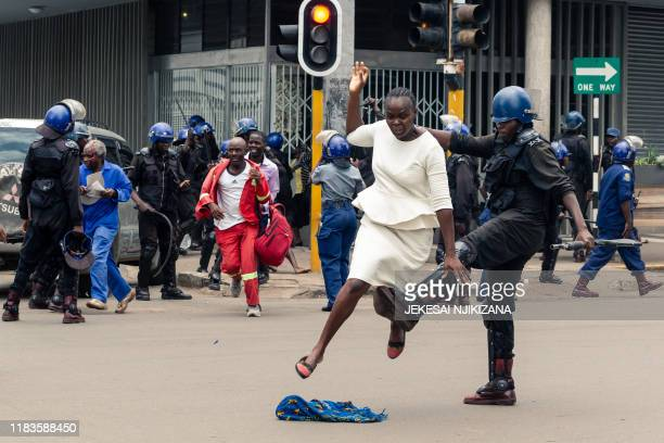 TOPSHOT An antiriot police man in Zimbabwe tackles a woman with his boot as they dispersed a crowd gathered to hear an address by leader of the MDC...