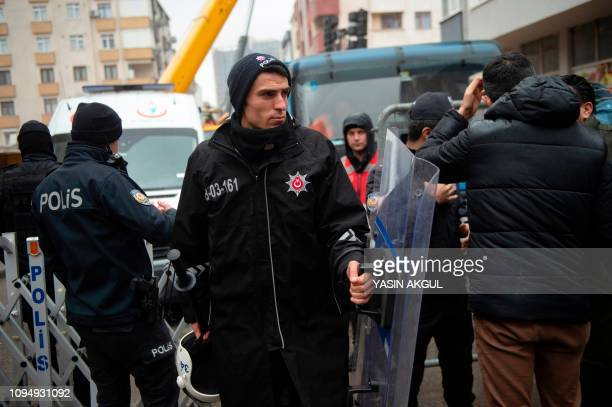 An antiriot policeman patrols as rescue workers search for victims after an eightstorey building collapsed the previous day in the Kartal district of...