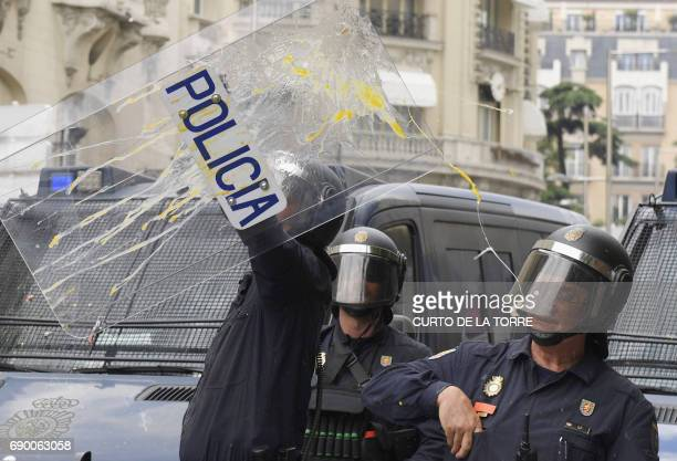 An antiriot policeman raises his sheild to stop a flying egg during a taxi strike action held between Atocha Train station to Neptuno Square in...