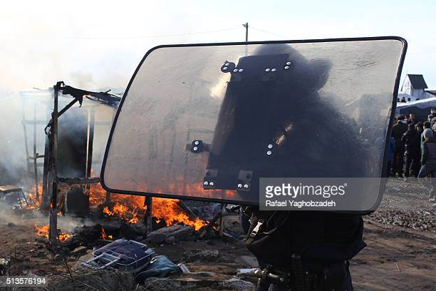 An antiriot policeman stands by destroyed shelters in the camp known as the Jungle March 3 2016 in the northern port city of Calais France Police and...