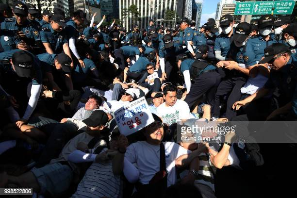 An antisamesexuality protester who try to block a parade are taken away by police officers during a parade of the Korea Queer Culture Festival 2018...