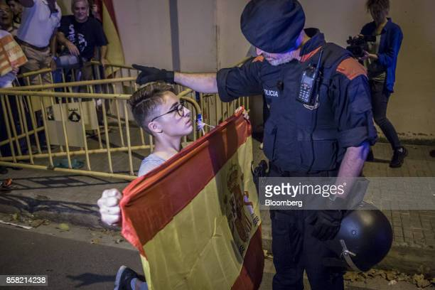 An antiseparatist demonstrator in support of the Spanish National Police and Civil Guard holds a Spanish national flag as he kneels in front of a...