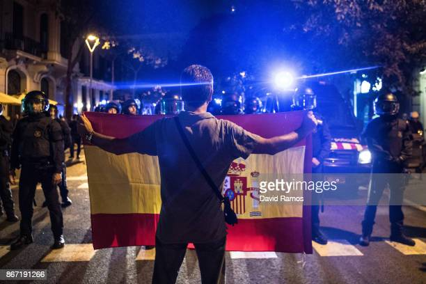 An antiseparatists demonstrator shows a Spanish flag to Catalan Riot Police officers during a march against the independence from Spain approved by...