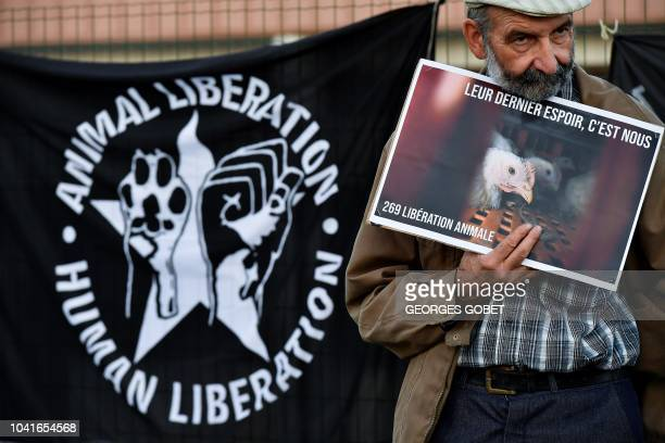 An antispeciesist activist from the Association 269Life Liberation Animale holds a banner reading 'Their last hope it's us' as part of an action...