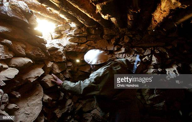 An antiTaliban fighter looks over a former Al Qaeda cave December 26 2001 deep in the Tora Bora valley of Afghanistan The cave was partially...