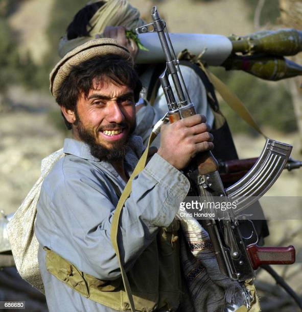 An antiTaliban soldier smiles while collecting his weapons December 11 2001 in the Tora Bora area of Afghanistan AntiTaliban forces made more gains...