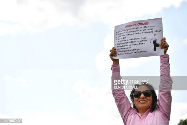 An antiTrump demonstrator holds a placard outside Buckingham Palace in central London on June 3 on the first day of the US President Donald Trump and...