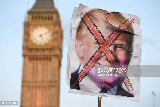 An antiTrump placard is pictured near the Houses of Parliament as an antiTrump protest gets underway in London on February 20 as parliament debates...