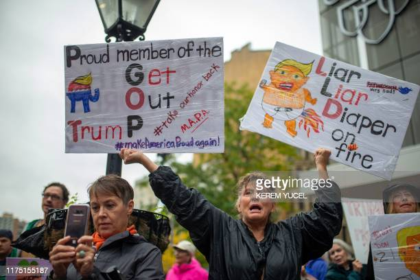 An antiTrump protester holds signs outside the Target Center in Minneapolis Minnesota ahead of a Keep America Great rally by the US president on...