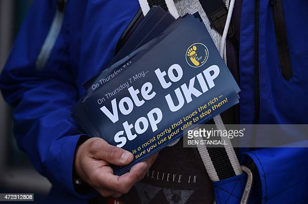 An antiUK Independence Party protester hold leaflets as UK Independence Party leader Nigel Farage takes part in a campaign visit to Ramsgate in Kent...