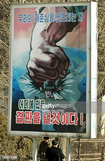 An antiUS propaganda poster showing a fist crushing a US soldier is shown on the streets of the North Korea capital Pyongyang on February 27 2008...