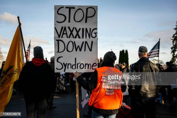 """An anti-vaccination activist holds a sign reading """"Stop vexing Down syndrome"""" as conservative demonstrators gather at the Washington State Capitol..."""
