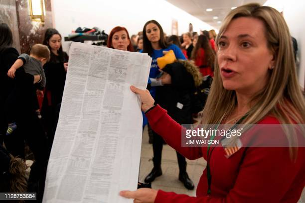 An AntiVaccination parent holds up a prescription document as she waits with others to get into a hearing where Ethan Lindenberger a student at...