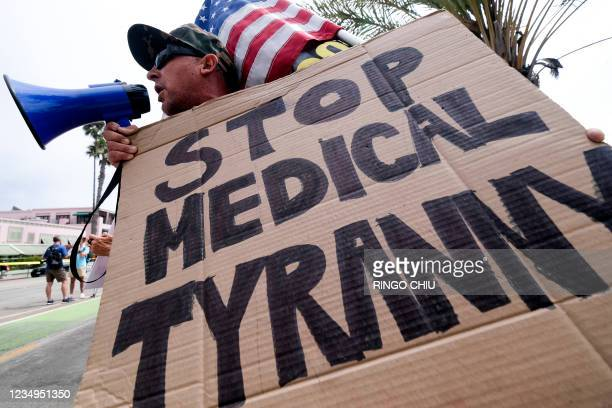An anti-vaccination protester holds a sign and a flag as he takes part in a rally against Covid-19 vaccine mandates, in Santa Monica, California, on...