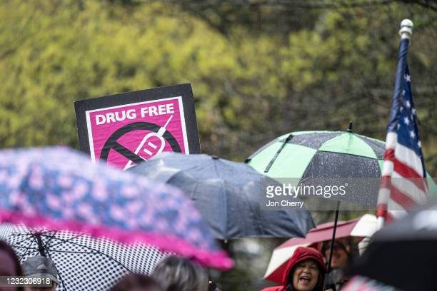 An anti-vaccination sign is seen above a row of umbrellas while demonstrators chant with speakers during a protest on state capitol grounds on April...