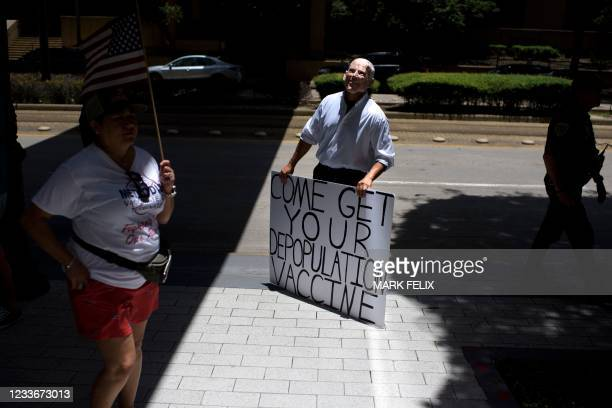 An anti-vaccine rally protester dressed up as Joe Biden holds a sign outside of Houston Methodist Hospital in Houston, Texas, on June 26, 2021. - A...