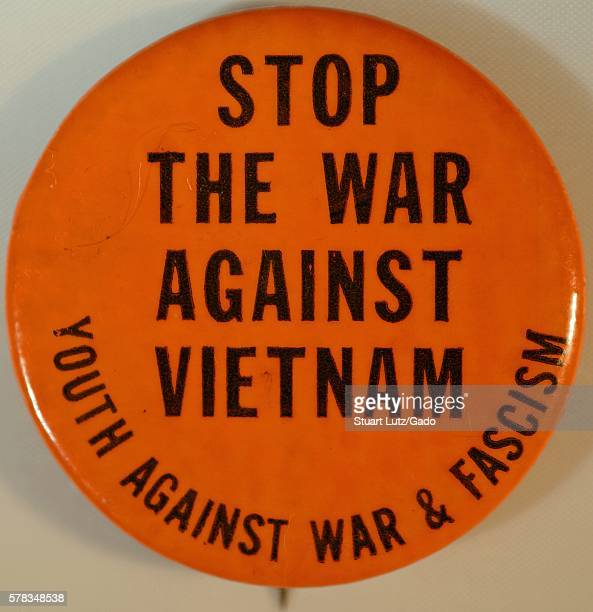 An antiVietnam War protest pin that has an orange background and contains the text 'Stop the war on Vietnam' the pin also includes text that reads...