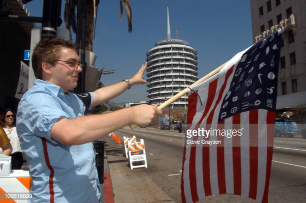An AntiWar Activists protests at the corner of Hollywood and Vine near the Capitol Records building waving an American flag with corporate logos in...